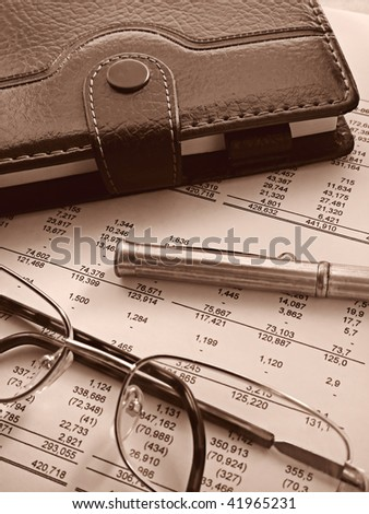 organizer, pen and glasses on financial statement - stock photo