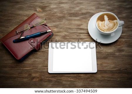 organizer, tablet, glasses and a cup of cappuccino on a wooden table - stock photo
