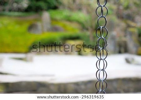 Oriental background. Rain chain in formal japanese garden, garden grounds out of focus, space for your text - stock photo