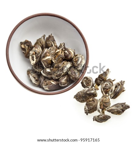 Oriental clay tea cup  with green  tea leaves isolated on white background - stock photo
