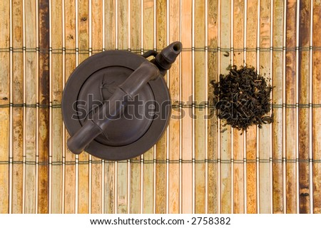 Oriental Clay Teapot with Loose Tea Leaves Top View on Green Bamboo Background - stock photo
