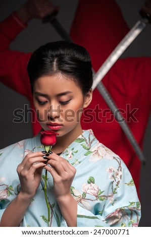 Oriental culture and traditions. Young beautiful Japanese woman in kimono holding a rose while standing against grey background with traditional ninja warrior with two swords - stock photo