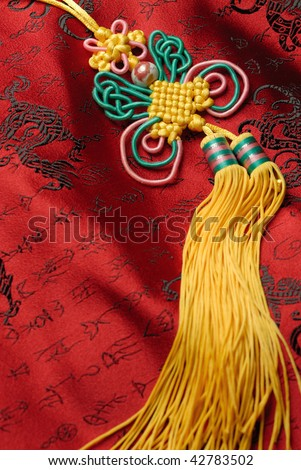 Oriental handicraft,Traditional lucky knot on Jin-Silk background.lucky Chinese knot pray the safety and property for the owner. - stock photo