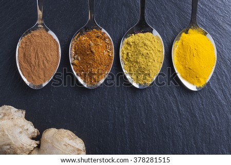 oriental indian spices curry paprika nutmeg on slate - stock photo