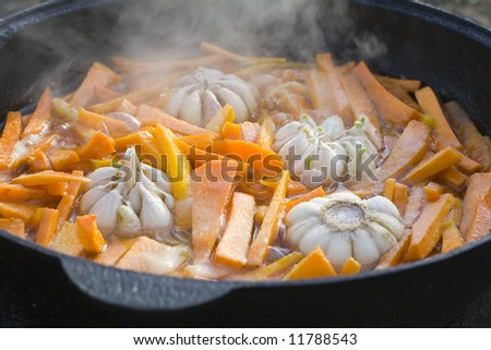 Oriental kitchen - fried carrot with garlic bulbs in big cauldron during the cooking process