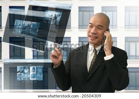 Oriental looking bald business man on phone and internet