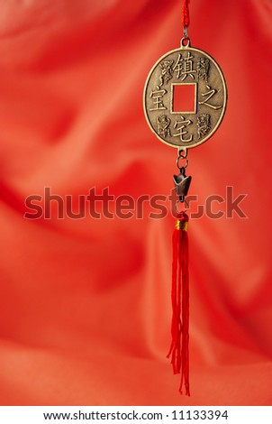 Oriental medallion on the red silk background - stock photo