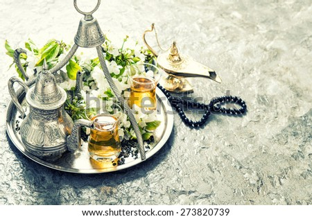 Oriental silver tea tableware, arabian lantern and rosary. Islamic holidays decoration. Vintage style toned picture - stock photo