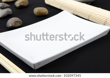Oriental Table Set-Up - Table set-up with rectangular platter, chopsticks, pebbles and straw mat on a black tablecloth. Shallow DOF.