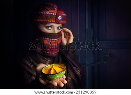 Oriental woman in turban offering yellow spice turmeric powder at bazar - stock photo