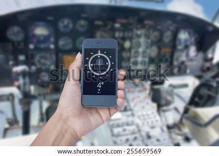 Orientation Concept a Hand Holding a Compass on smart phone in control room helicopter  - stock photo