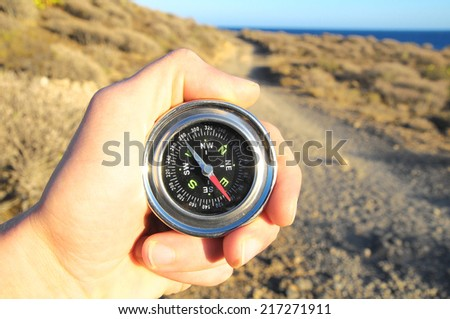 Orientation Concept a Male Hand Holding a Metal Compass - stock photo