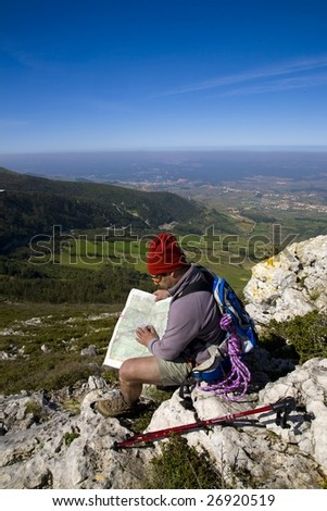 Orienteering - A trekker consulting a map, alone on a mountain, over a clear blue sky - stock photo