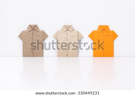 origami a man's shirt on a white background orange brown of paper - stock photo