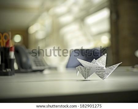 Origami bird on desk - stock photo