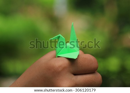 Origami Bird on Woman's hands - stock photo