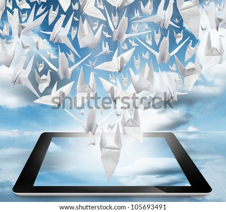 Origami Birds in flight on tablet pc computer on blue sky - stock photo