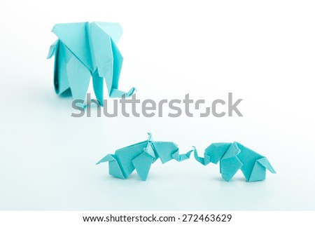 Origami blue elephant family on white background.Baby elephant playing with mum watching in  the background - stock photo