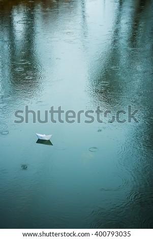 origami boat on wet asphalt during rain in summer - stock photo