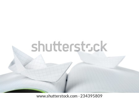 Origami boats on notebook, on white background
