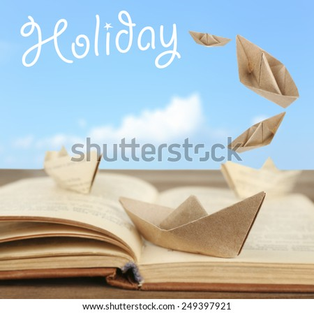 Origami boats on old book on sky background - stock photo
