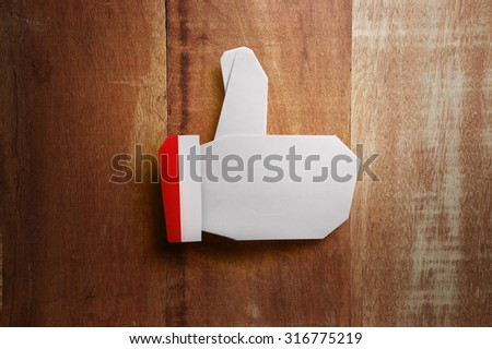 Origami Christmas thumbs up icon on wooden background - stock photo