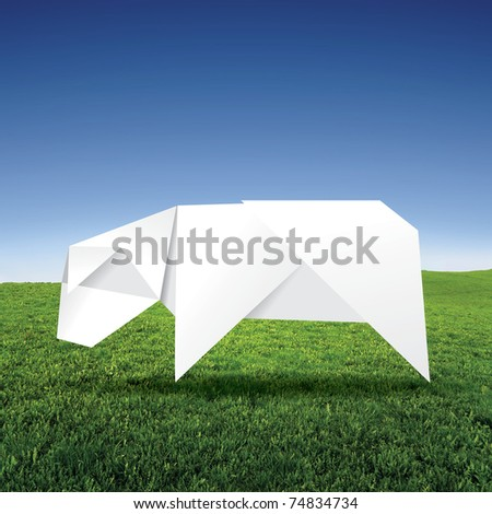 origami cow on grass field - stock photo