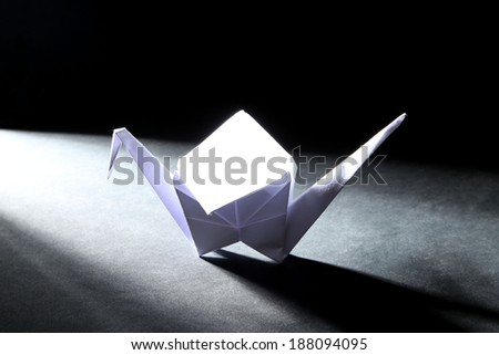 Origami crane on dark background with light - stock photo
