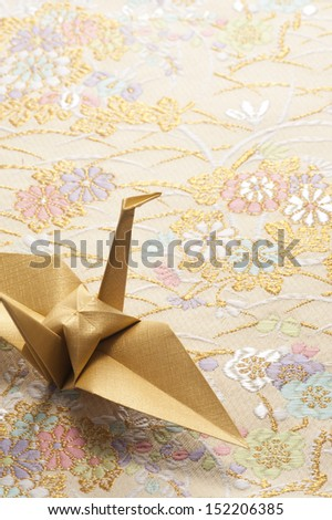 origami crane on japanese textile background - stock photo