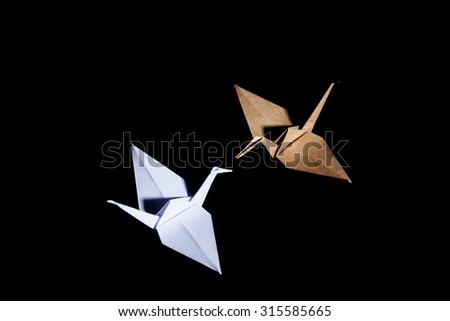 Origami cranes made from brown and white recycle paper on black background. - stock photo