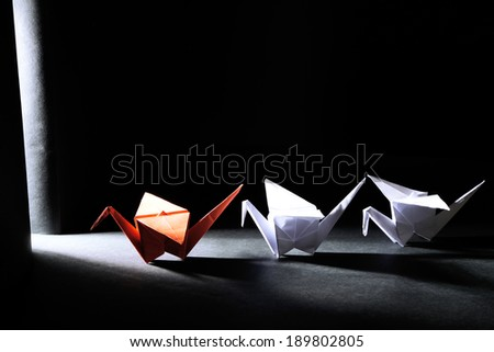Origami cranes on dark background with light - stock photo