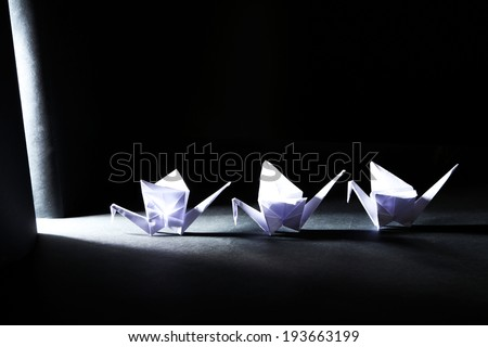Origami cranes on dark background with light - stock photo