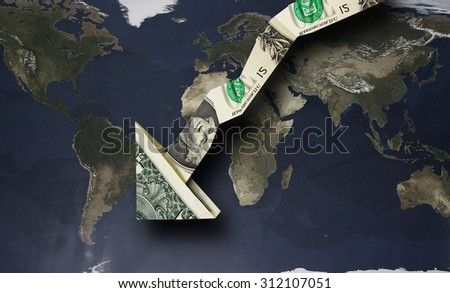 Origami dollar arrow pointing down over a world map               - stock photo