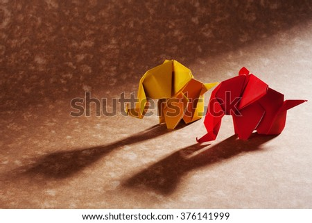 Origami elephants, made of orange and red paper with shadows over craft background. - stock photo