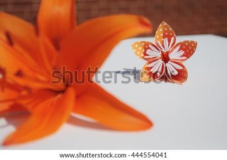Origami flower behind orange lily flower. - stock photo