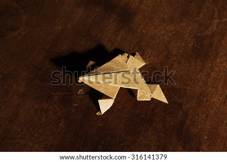 Origami frog isolated on wooden background - stock photo