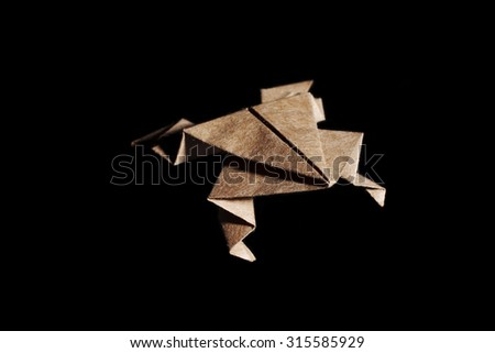 Origami frog made from brown paper isolated on black background - stock photo