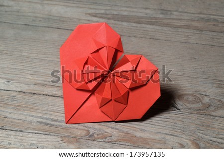 Origami heart on wooden background