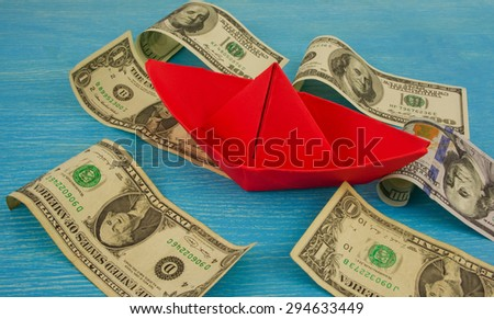 Origami paper boat at sea of money / american moneys of hundred dollar on background - stock photo