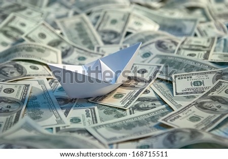 Origami paper boat at sea of money / studio photography of american moneys of hundred dollar on background