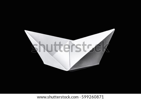 Origami paper boat isolated on black background
