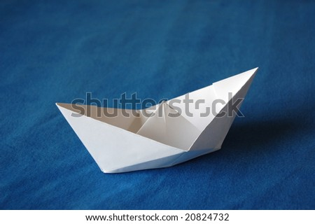 origami paper boat isolated on blue water - stock photo
