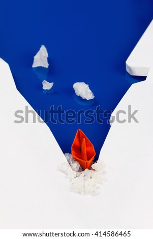 Origami paper boat on water as an icebreaker, ice punched. Concept of success, moving forward, overcoming difficulties - stock photo