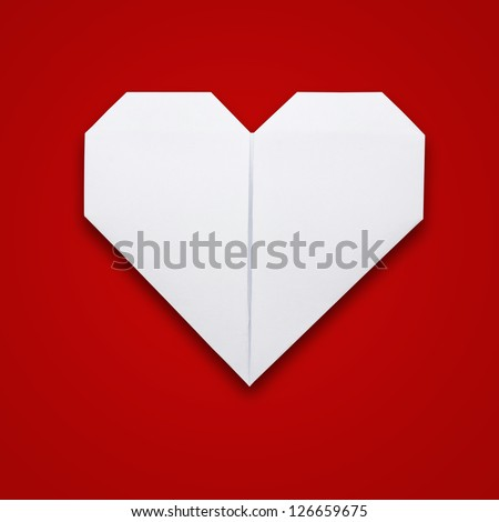Origami paper heart shape on red background - stock photo