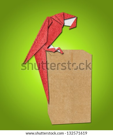 origami parrot made of paper on green background - stock photo