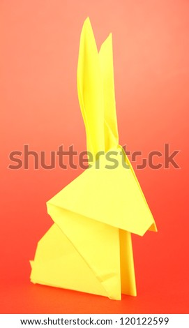 Origami rabbit on red background