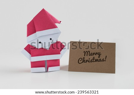 Origami Santa Claus paper craft with a merry christmas card - stock photo