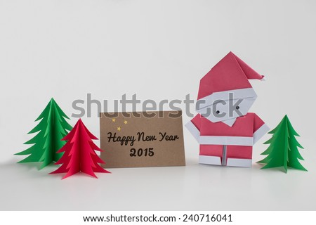 Origami Santa Claus paper craft with christmas trees and a Happy New Year 2015 card - stock photo