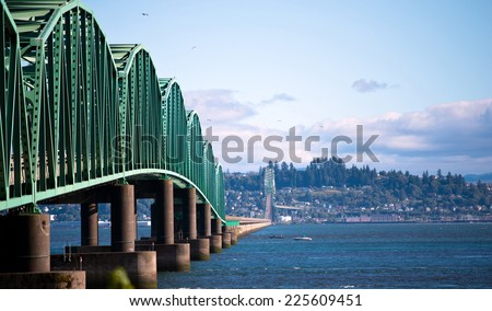 Original and unique engineering solution bridge across the Columbia River in Astoria, bridge made of steel trusses on concrete backwaters for large ships, and the road in the middle of the river. - stock photo