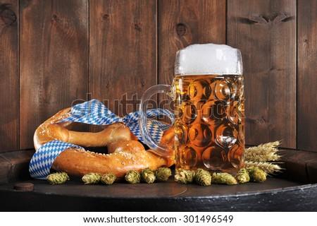 original bavarian Oktoberfest big soft pretzel with beer mug, hops and wheat from Germany on old beer barrel - stock photo
